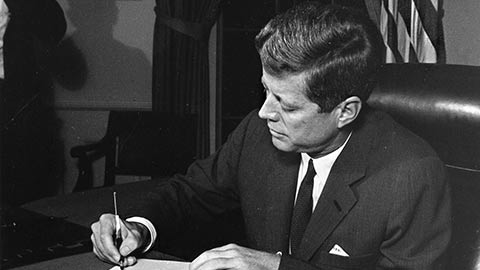 President Kennedy signs a document.